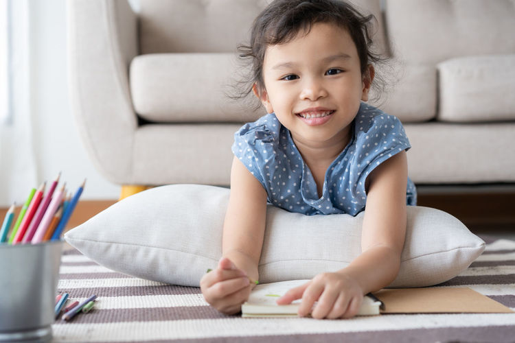 Portrait of smiling girl with book lying on rug