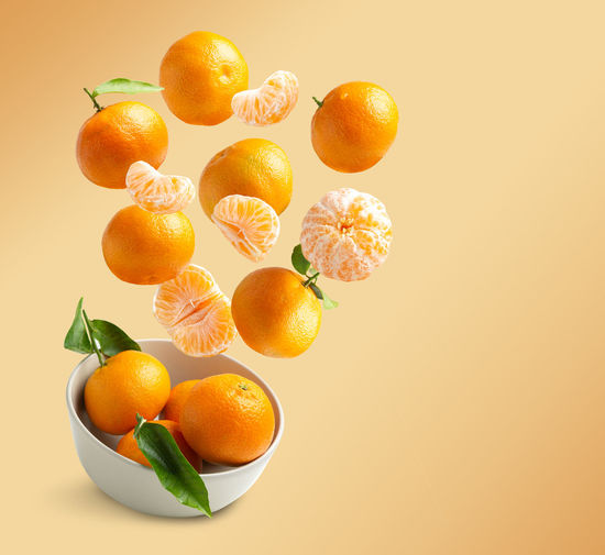 High angle view of orange fruit against white background