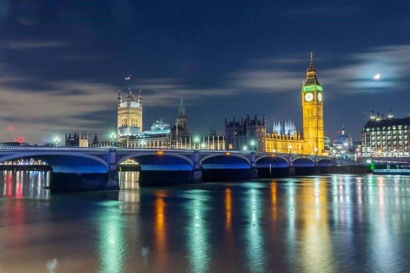 Westminster bridge over thames river by illuminated big ben and city at night