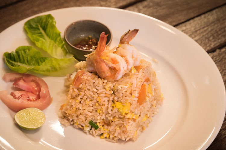 Stir fried rice served in a white dish and serve Close-up Crustacean Food Food And Drink Freshness Fruit Garnish Healthy Eating Herb High Angle View Indoors  Meal Meat No People Plate Prawn Ready-to-eat Rice - Food Staple Seafood Serving Size Table Vegetable Wellbeing