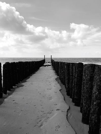 Wooden posts on sand against sea at beach