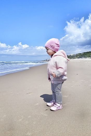 Side view of cute girl wearing warm clothing at beach against sky