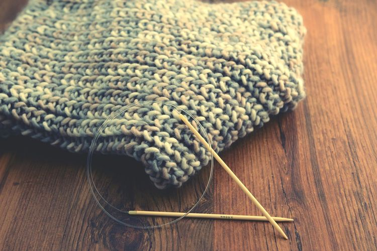 Knitting Needles With Scarf On Wooden Table