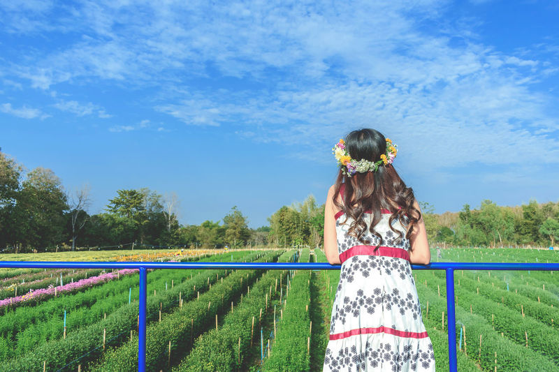 Rear view of woman standing by railing over farm against sky