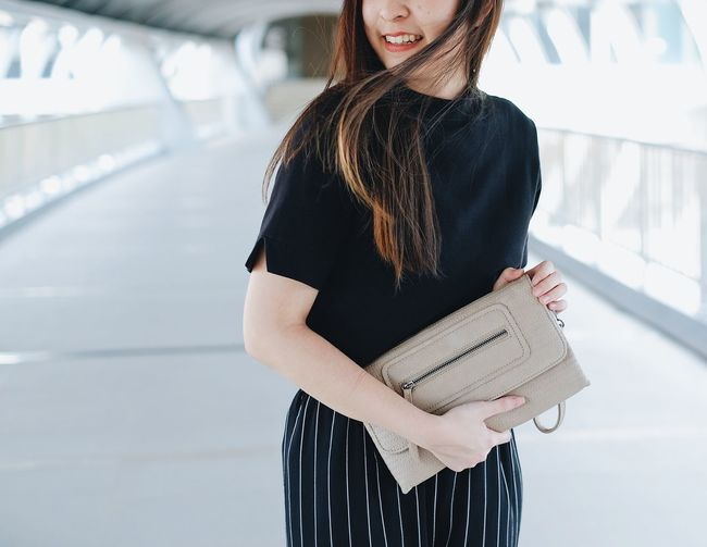 Standing One Person Long Hair Focus On Foreground Hairstyle Real People Women Young Adult Holding Casual Clothing Hair Adult Young Women Lifestyles Three Quarter Length Day Indoors  Midsection Beautiful Woman Fashion Smile Style Minimal Bag Hand Bag