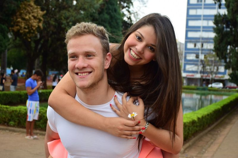 Smiling Young Man Piggybacking Girlfriend In City