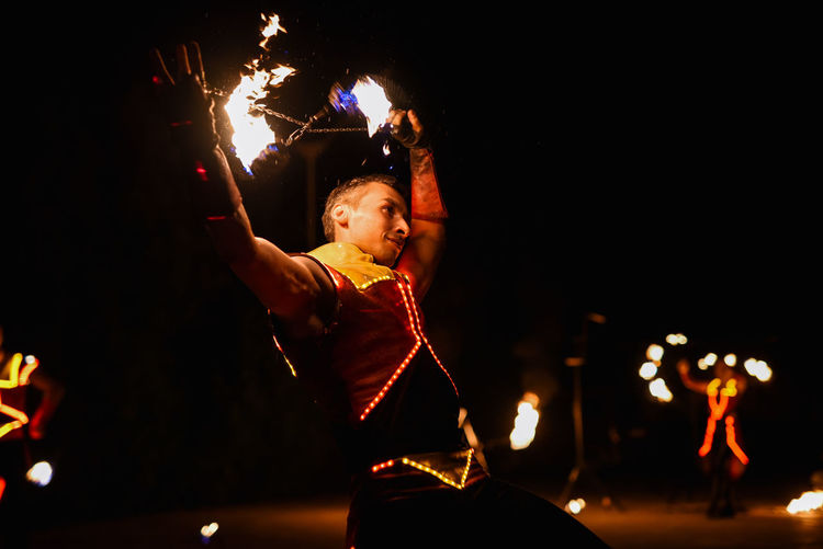 Man holding illuminated fire at night