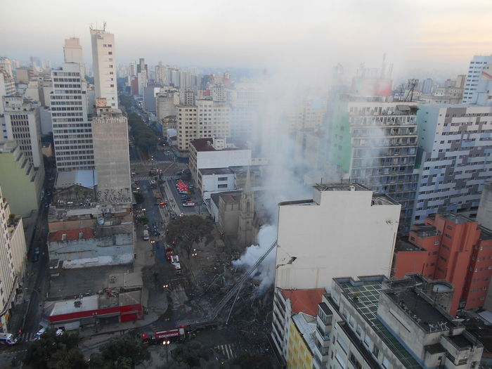 Daylight begins. Building Collapse: Inner City Calamity in downtown São Paulo at Largo do Paissandú; 3 am May 1, 2018. The abandoned former Federal Police steel and glass skyscraper, which had been invaded by street people, imploded this early morning and the neighboring buildings, including the Lutheran Church on Avenida Rio Branco, were destroyed by fire as well. This photo taken between 6 am to 8 am on May 1, 2018 at Largo do Paissandú. Current Events Destruction Largo Do Paissandu May 1, 2018 Susan A. Case Sabir Unretouched Photography About 7 Am Building Collapse Building Fire Building Implosion Burning Building Controlled Chaos Dangerous Situation Downtown São Paulo Early Morning Firefighters Firefighters In Action Helicopters Overhead High Angle View Implosion Responsiveness Smoke - Physical Structure Unexpected Event Urban Photography Urban Strife