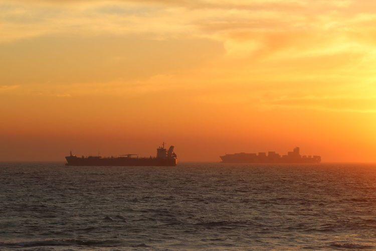 Silhouette container ships in sea against orange sky during sunset