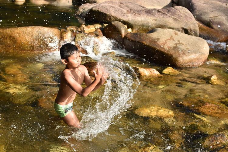 Full length of shirtless boy in river