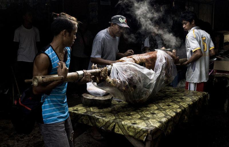 Men Cooking Pork On Table