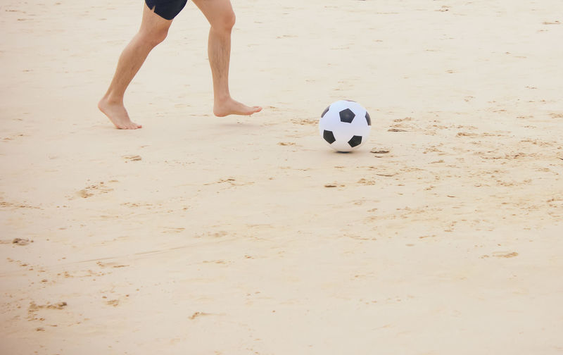 Low section of man playing with soccer ball at beach