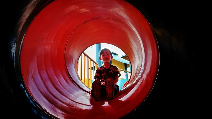 Girl sitting on red slide at playground
