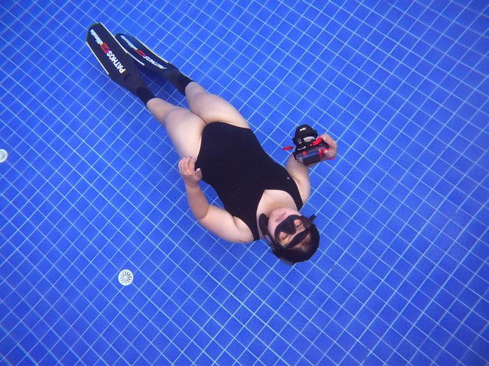 High angle view of woman lying on swimming pool