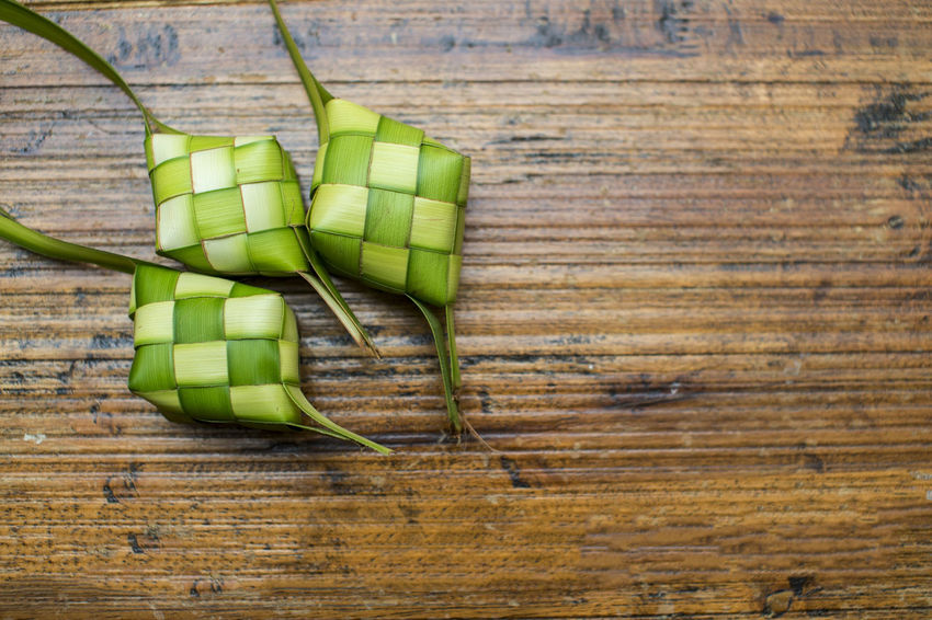 Ketupat or rice dumpling on wooden background ASIA Casing Close-up Coconut Leaf Day Dumpling Rice Eid Mubarak Fasting Festival Food Food And Drink Freshness Green Color Hari Raya Aidilfitri Healthy Eating Indoors  Ketupat Malaysia Culture Muslim Oriental Ramadan  Raw Food Table Vegetable Wood - Material