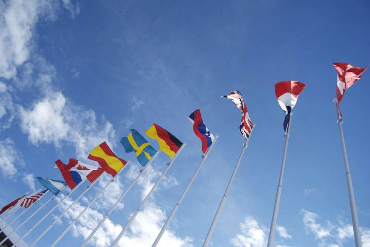 Low Angle View Of Various Flags Against Sky