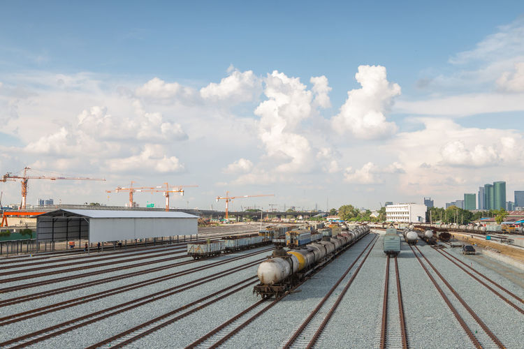 Trains on railroad tracks in city against cloudy sky
