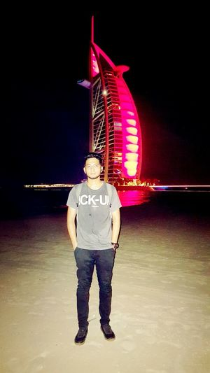 Full length of man standing by illuminated built structure against sky at night
