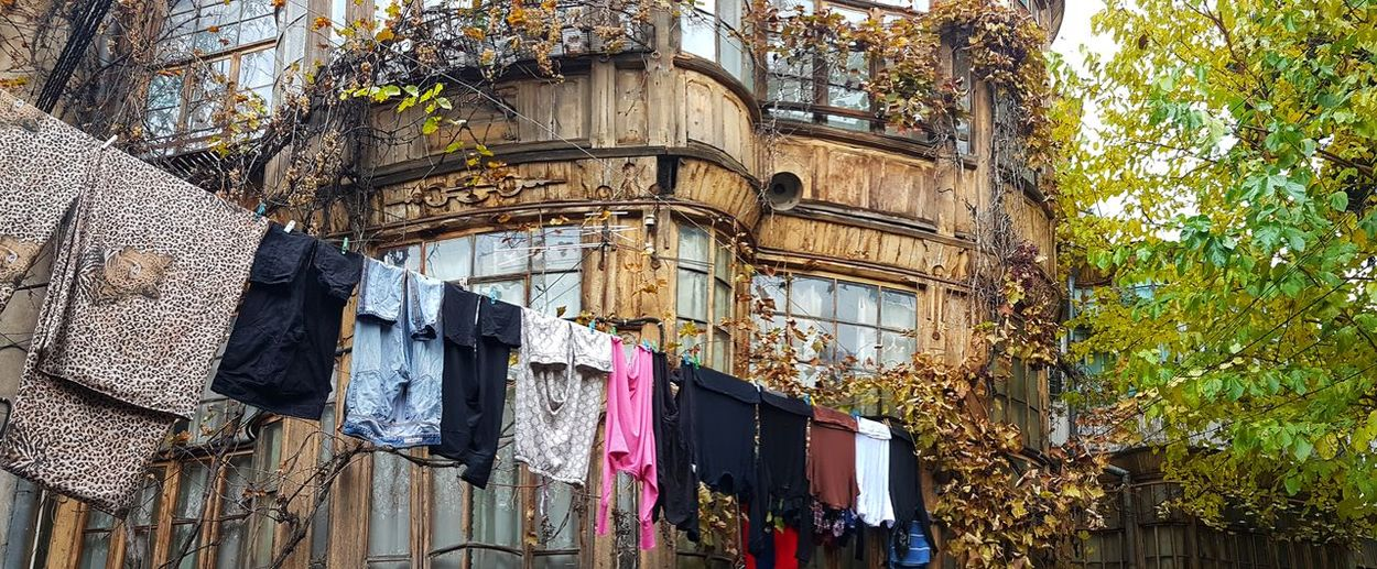 Laundry makes the yards of Tbilisi more colorful Hanging Architecture Low Angle View Building Exterior Built Structure Window No People Day Outdoors Tree Autumn Leaves Autumn Street Photography Autumn Colors Streetphotography Tbilisi Georgia Tbilisi Architectural Column Architecture The Still Life Photographer - 2018 EyeEm Awards