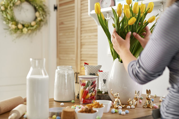 Midsection of woman holding flowers in vase on table