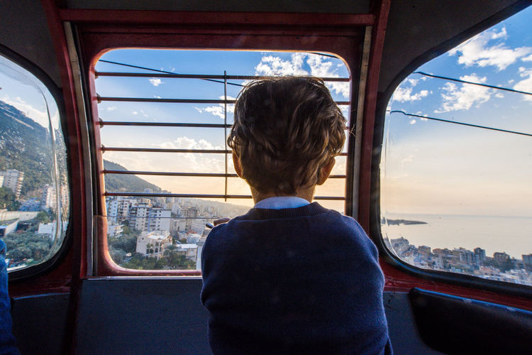Rear view of boy looking through cable car window