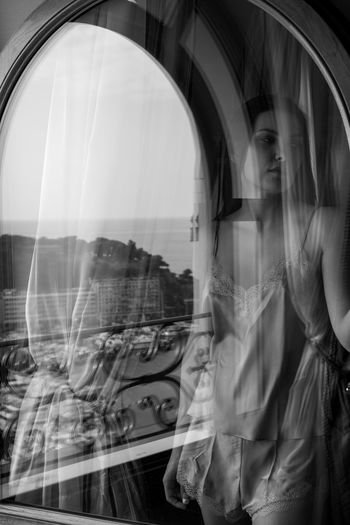 Digital composite image of woman with reflection on glass window