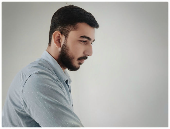Side view of young bearded man against white background