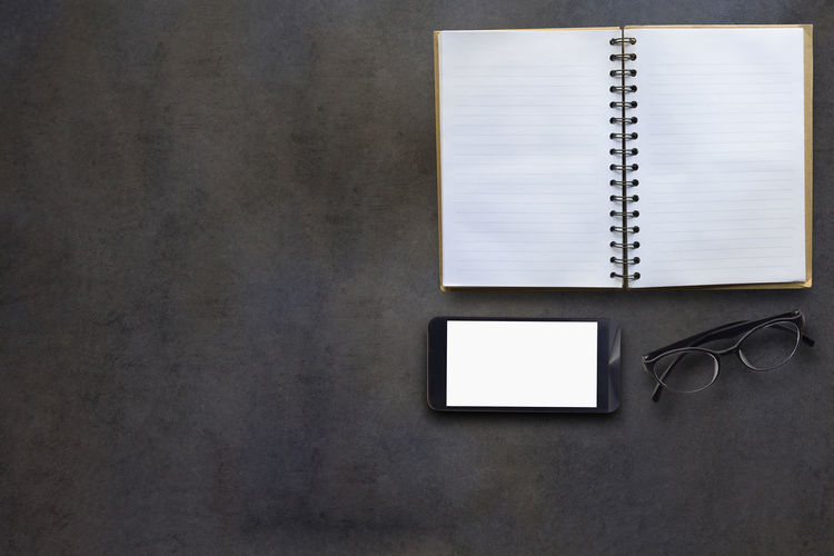 Directly above shot of open book with smart phone and eyeglasses on table