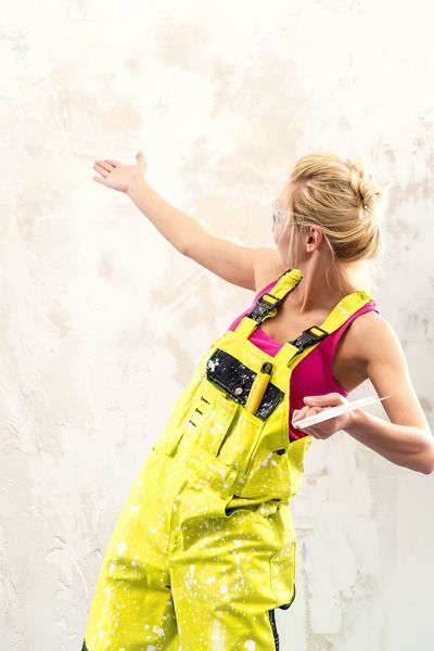 Female construction worker with putty knife over obsolete background Construction Industry Woman WorkWear Worker Blond Hair Builder Built Structure Caucasian Construction Worker Coverall Employment Female Gesture Hand Handywoman Human Job Labor Overall Professional Occupation Protective Workwear Repair Repair Woman Spatula