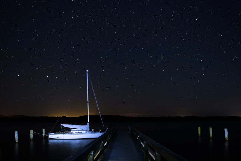 Boats Moored At Harbor Against Sky At Night