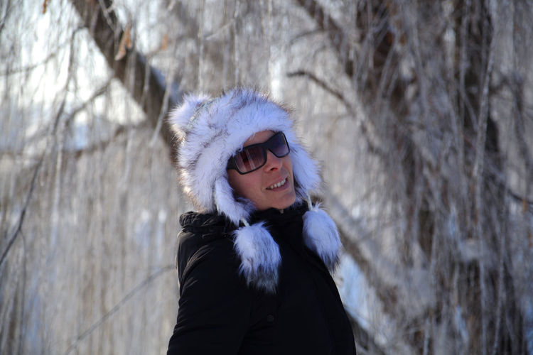 Portrait of woman wearing fur hat standing outdoors during winter