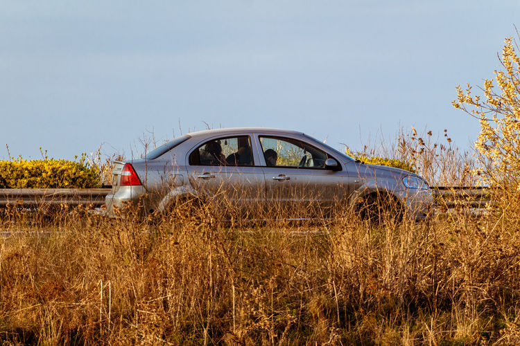 Abandoned car on field against clear sky