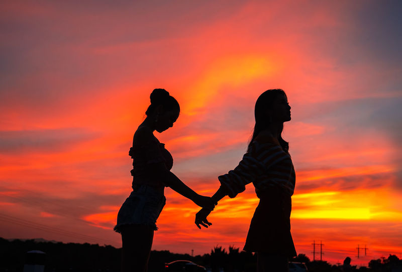 Romantic couple standing outdoors at a colourful sunset on a background and silhouette. Sunset Orange Color Silhouette Sky Two People Cloud - Sky Togetherness Adult Women Men Beauty In Nature Bonding Lifestyles Standing Real People Side View Nature People Leisure Activity Positive Emotion Outdoors Couple - Relationship Handshake Sweetheart Girlfriends