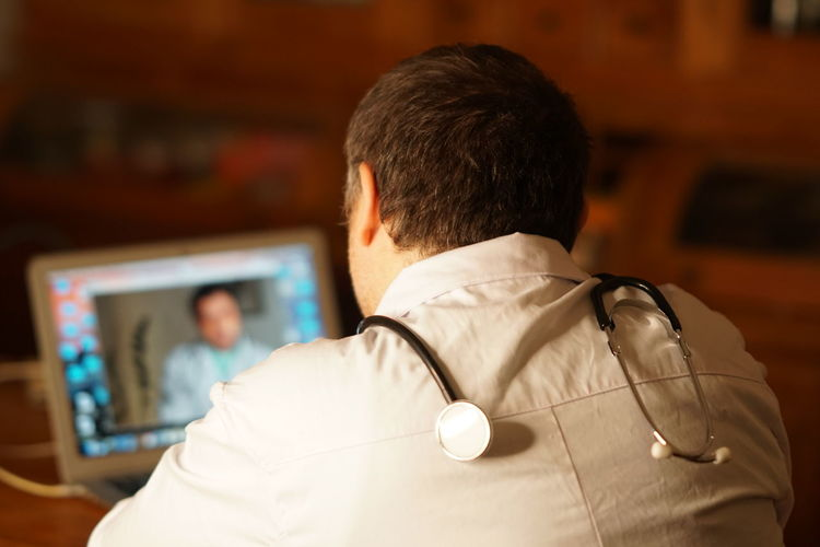 At Work Doctor  Man Working Adult Close-up Communication Connection Focus On Foreground Headshot Indoors  Medical Occupation One Person People Person Professional Real People Rear View Stethoscope  Technology Wireless Technology