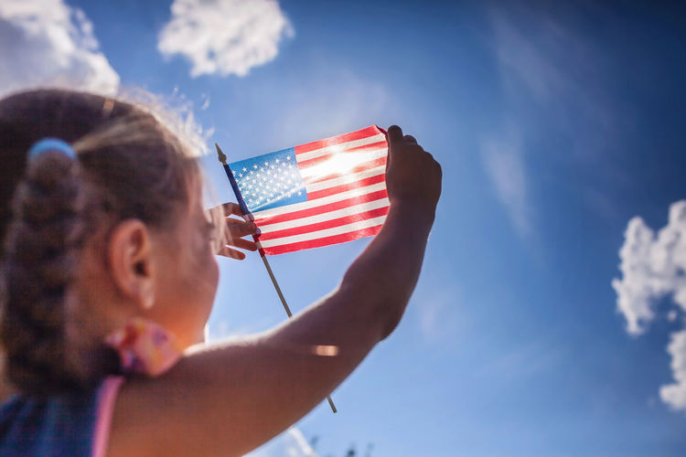 Patriot and national flag day celebration. little patriot sitting on the meadow and holding usa flag