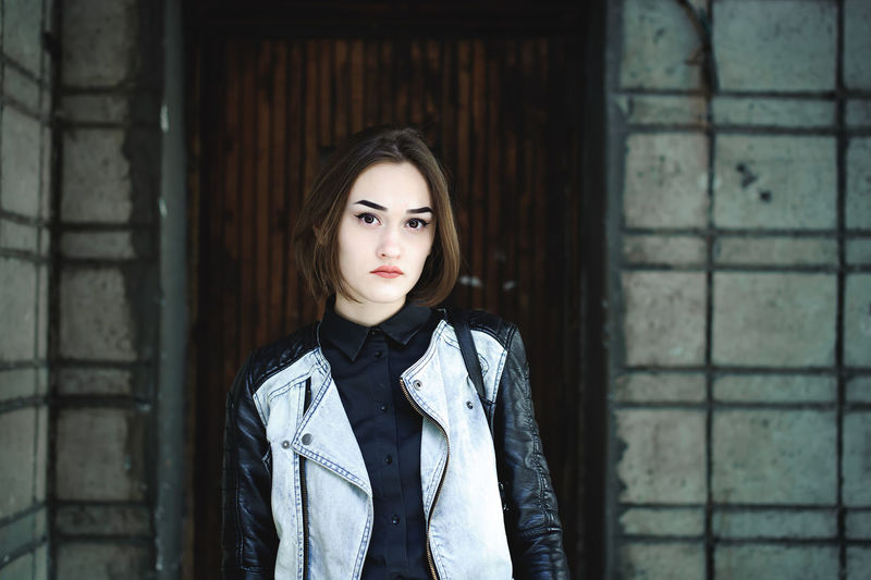 street portrait of a student girl, fashionably dressed in dark clothes, with a black backpack and a denim jacket Beautiful Woman Beauty Casual Clothing Day Fashion Front View Leisure Activity Lifestyles Looking At Camera One Person Outdoors People Portrait Real People Standing Waist Up Young Adult Young Women