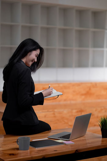 Asian business woman working at office and taking note, female sitting on desk and using laptop