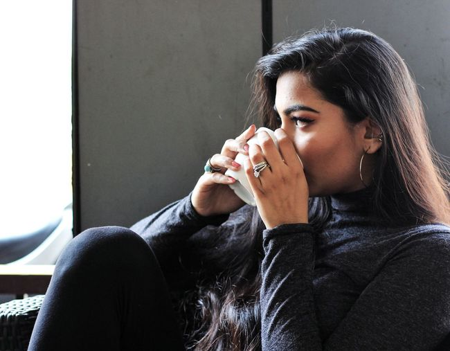 Thoughtful Young Woman Holding Coffee Cup In Cafe