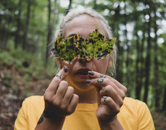 Close-up of woman holding leaf in forest