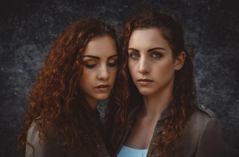 Portrait of siblings against wall
