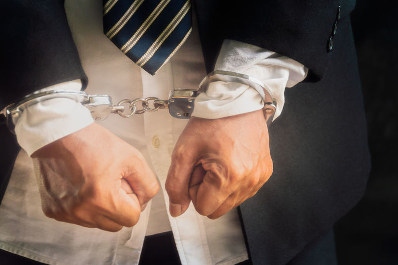 Midsection of business person with handcuffs