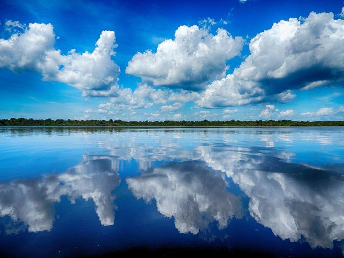 SCENIC VIEW OF Cloudy Sky Reflected In Lake Surrounded By Trees
