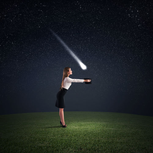 Full length of woman standing on field against sky at night