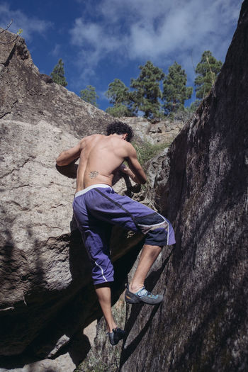 Rear view of shirtless man climbing on rock against sky
