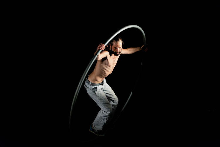 Circus Adult Black Background Casual Clothing Copy Space Dark Flexibility Front View Full Length Healthy Lifestyle Indoors  Lifestyles Mid Adult One Person Real People Standing Strength Studio Shot Young Adult Young Men