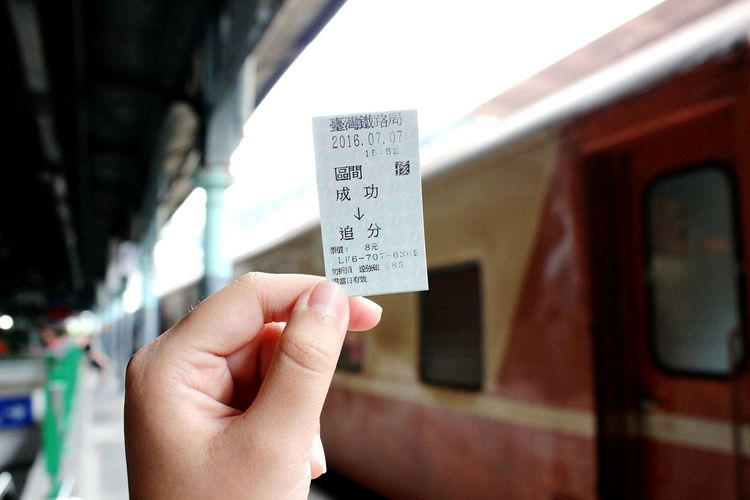Cropped hand of person holding ticket at railroad station platform