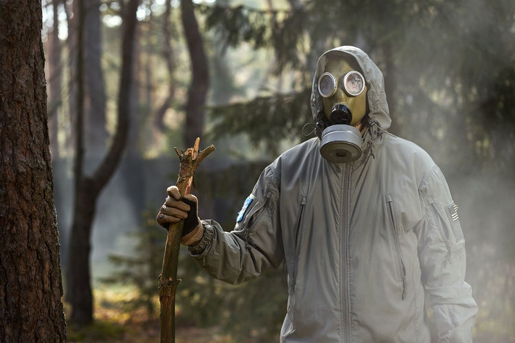 Person wearing mask against trees in forest
