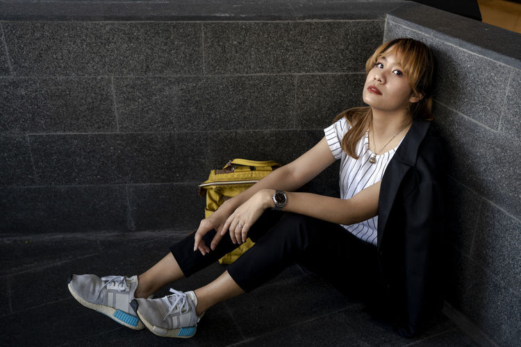 Portrait of businesswoman sitting by wall