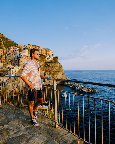 Full length of man standing by railing against sea