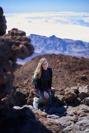 Young woman sitting on rock against mountain